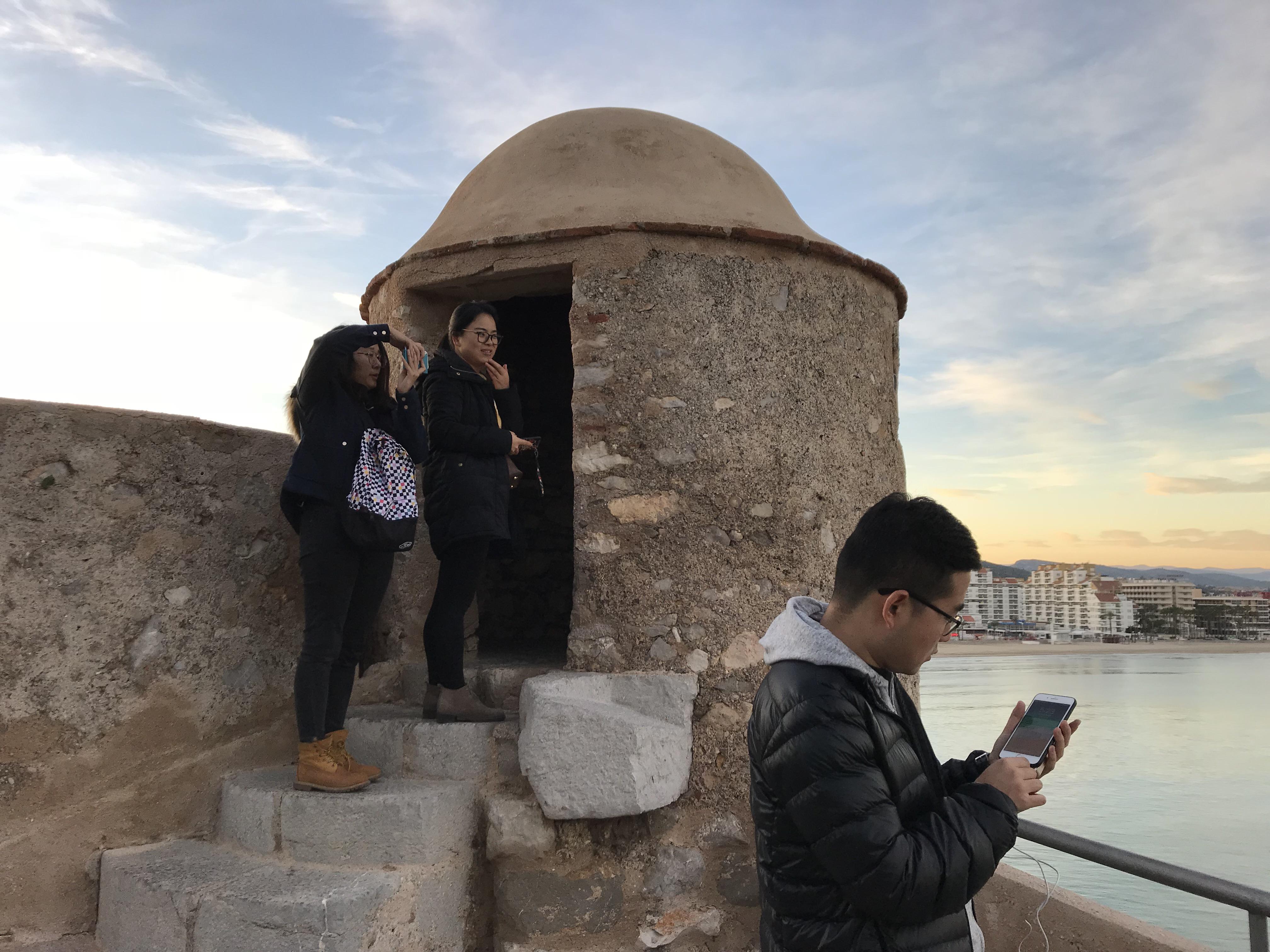 Turistas chinos en Peñíscola usando sus móviles