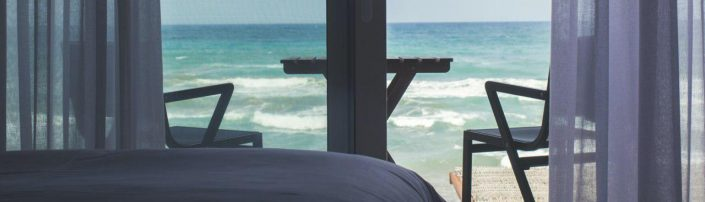 cama y ventana de hotel de playa 1500x430