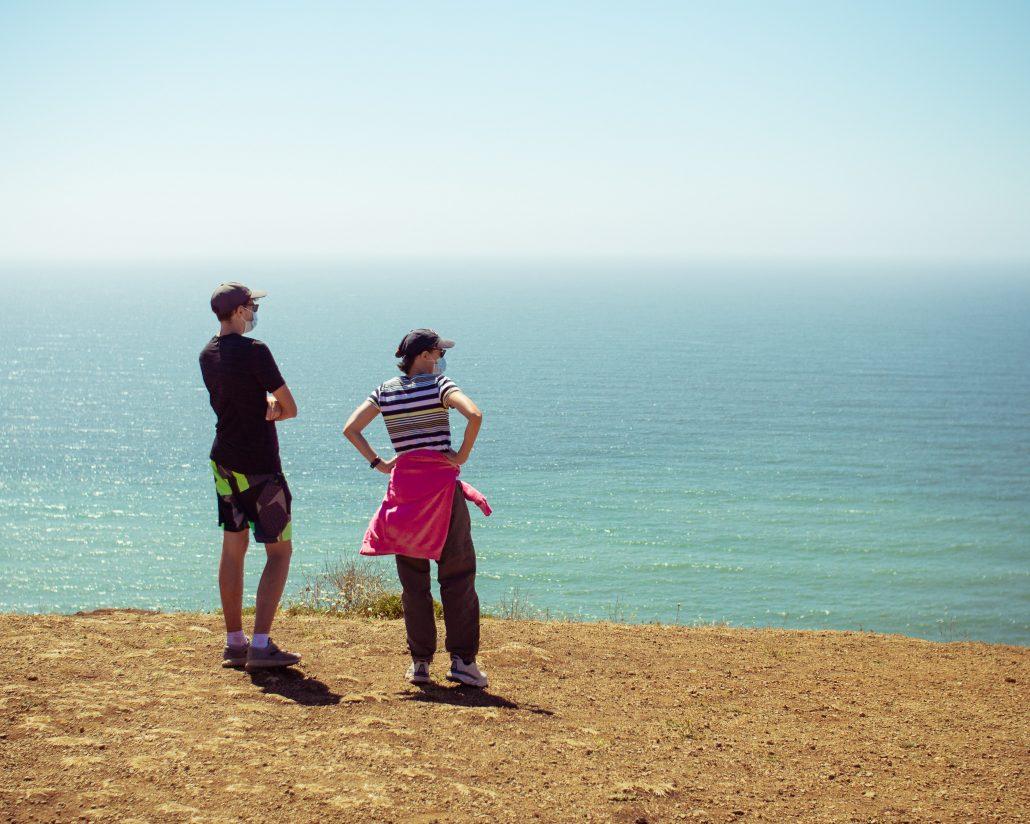 pareja con mascarilla mirando al mar